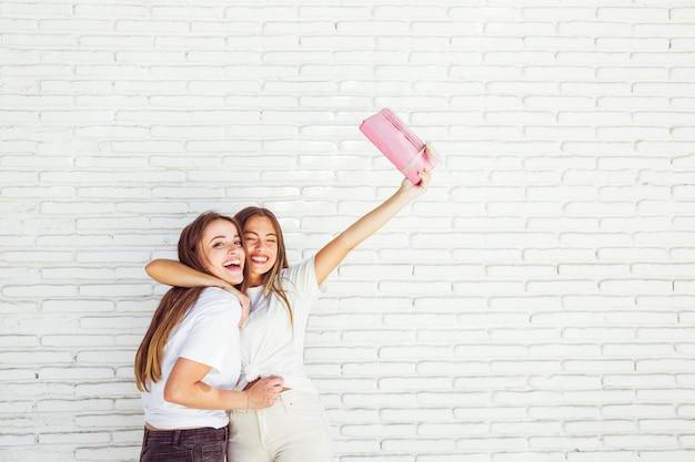Feliz mujer abrazando a su amiga y levantando sus brazos con un regalo