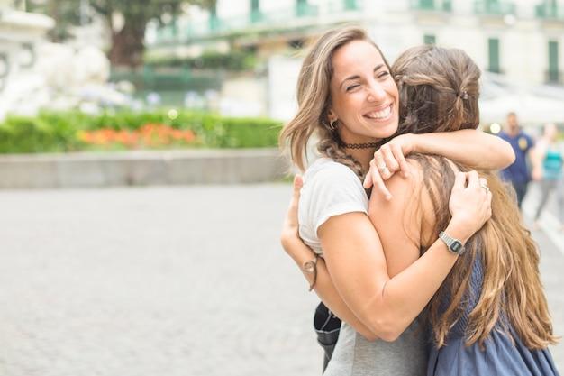 Feliz mujer abrazando a sus amigos al aire libre