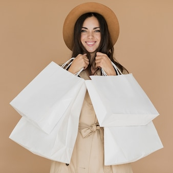 Feliz mujer en abrigo con muchas redes de compras