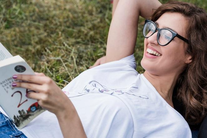 Feliz mujer acostada en el libro de lectura de hierba