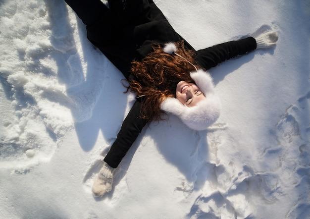 Feliz mujer adolescente acostada en la nieve profunda en el hermoso día de invierno