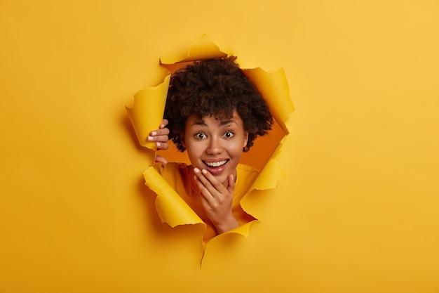 Feliz mujer adulta morena sostiene la barbilla, sonríe ampliamente, muestra un buen tratamiento dental, tiene una piel sana, se ve curiosamente feliz a través del agujero de papel rasgado, fondo amarillo brillante