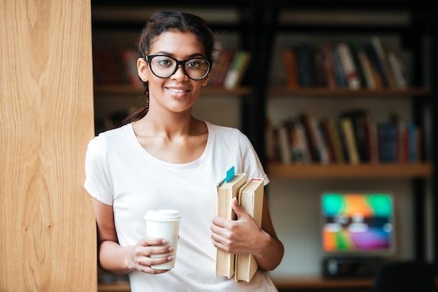 Feliz mujer africana con gafas de pie en la biblioteca