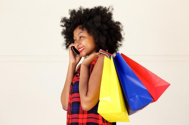 Feliz mujer africana hablando por teléfono con bolsas de compras