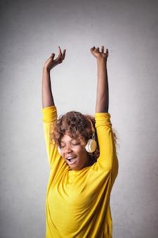 Feliz mujer afro disfrutando de la música.