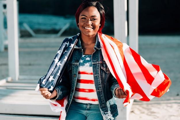 Feliz mujer afroamericana envuelta en la bandera de estados unidos