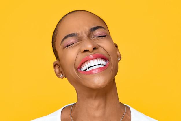Feliz mujer afroamericana extática sonriendo con los ojos cerrados aislados en la colorida pared amarilla