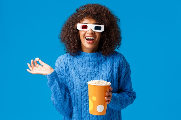 Feliz mujer afroamericana guapa divertida riendo a carcajadas, comiendo palomitas de maíz, viendo películas de comedia en gafas 3d, divirtiéndose, asistir al estreno en el cine, de pie en la pared azul