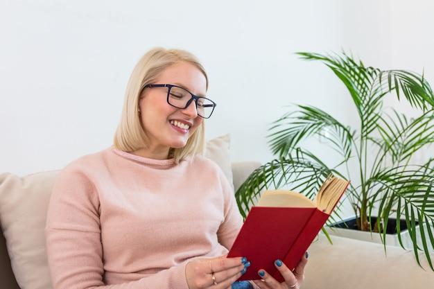 Feliz mujer albina relajante en casa en invierno acogedor o fin de semana de otoño con libro y taza de té caliente, sentado en el sofá