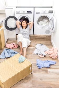 Feliz mujer ama de casa en el lavadero cerca de la lavadora con ropa sucia