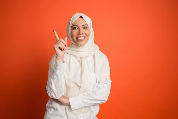 Feliz mujer árabe en hijab. retrato de niña sonriente, posando en el fondo rojo del estudio.