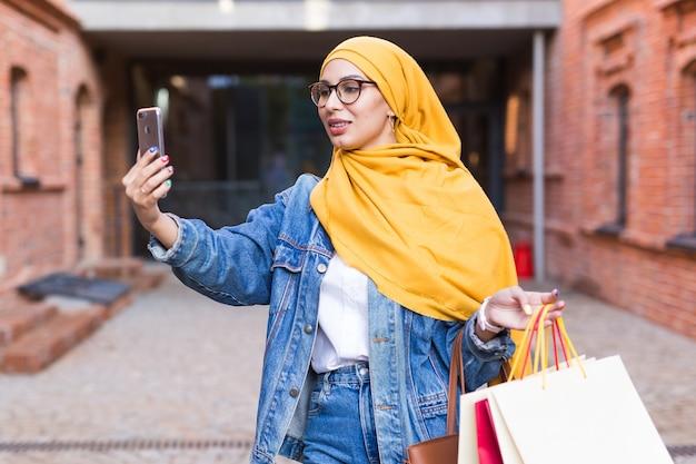 Feliz mujer árabe tomando selfie al aire libre después de ir de compras