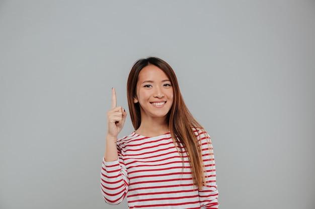 Feliz mujer asiática apuntando el dedo hacia arriba en el espacio de la copia
