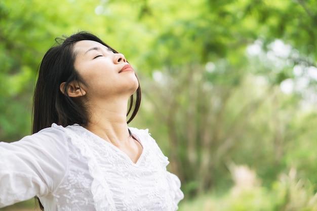 Feliz mujer asiática arma hasta relajarse con la naturaleza