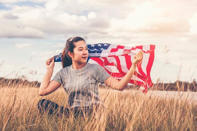 Feliz mujer asiática con bandera estadounidense usa celebra el 4 de julio