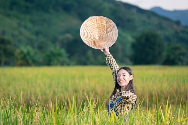 Feliz mujer asiática escribir notas en campos de arroz