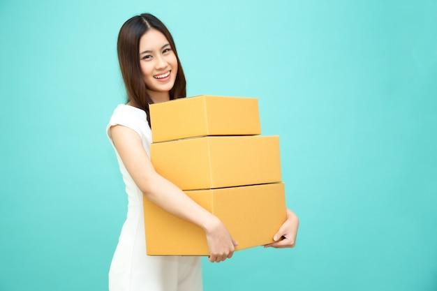 Feliz mujer asiática con paquete caja de paquetería, mensajería de entrega y concepto de servicio de envío