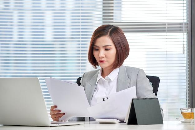 Feliz mujer asiática que trabaja en la oficina. mujer pasando por algunos trámites en el lugar de trabajo.