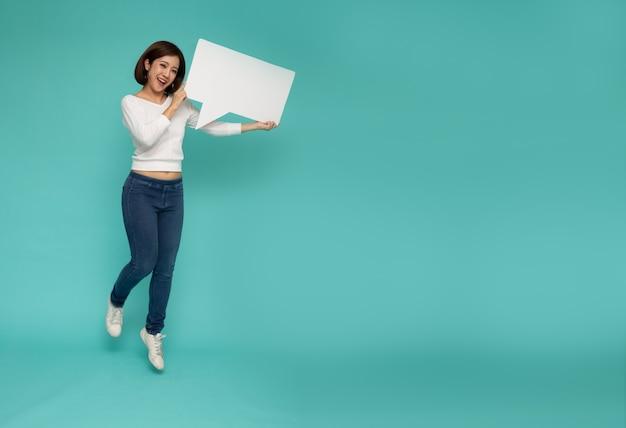 Feliz mujer asiática saltando con burbujas de discurso en blanco blanco aisladas en la pared verde claro con espacio de copia