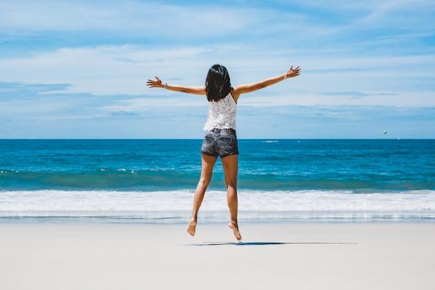 Feliz mujer asiática saltando en la playa