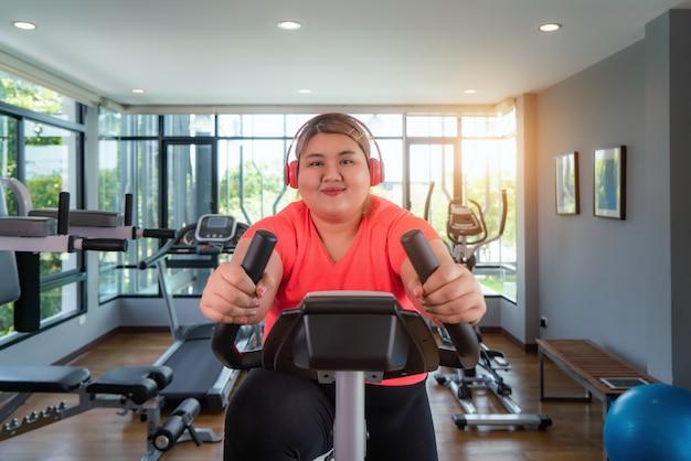Feliz mujer asiática con sobrepeso con entrenamiento de auriculares en bicicleta estática en el gimnasio moderno, feliz y sonríe durante el entrenamiento.