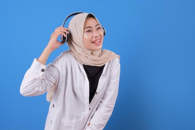 Feliz mujer asiática sonriendo escuchando música en auriculares