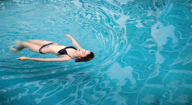 Feliz mujer asiática sonriendo en la piscina