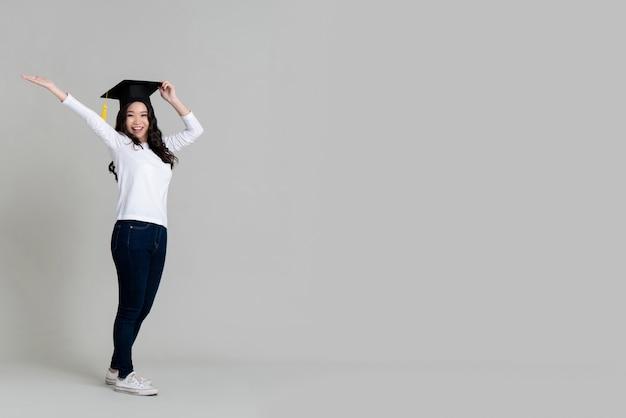 Feliz mujer asiática sonriendo y vistiendo gorra graduada