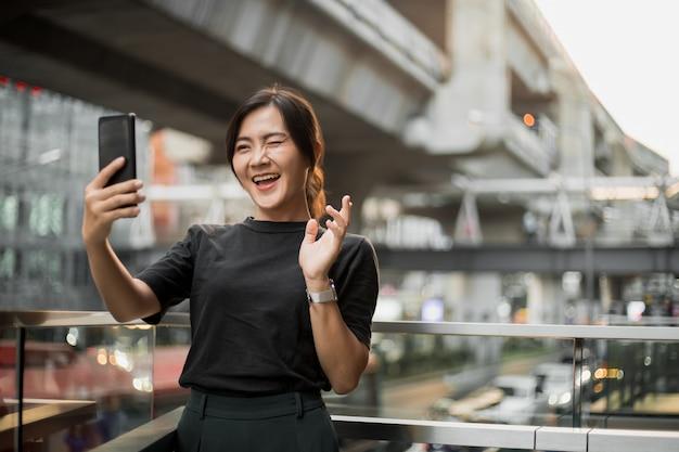 Feliz mujer asiática tomando un selfie en la ciudad