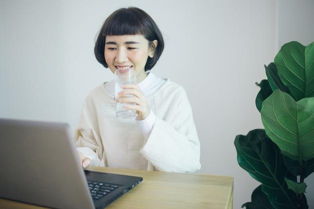 Feliz mujer asiática trabaja desde casa y agua potable