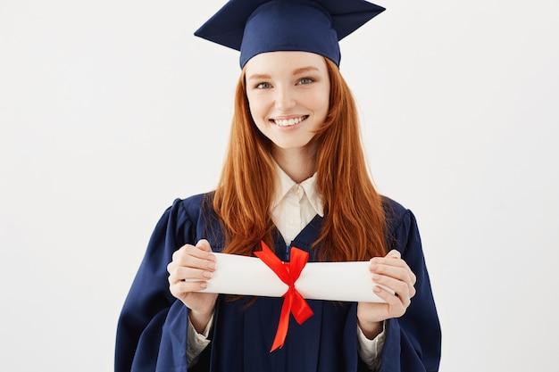 Feliz mujer astuta graduado en tapa sonriendo sosteniendo diploma.