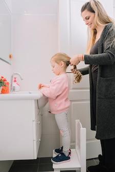 Feliz mujer atando el cabello de su hija