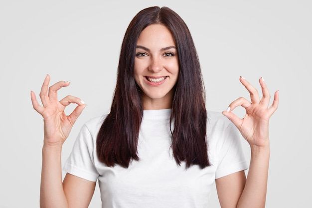 Feliz mujer atractiva con cabello largo y liso y oscuro, hace un buen signo con ambas manos, muestra aprobación