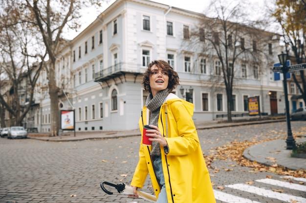 Feliz mujer bastante joven bebiendo café. mirando a un lado