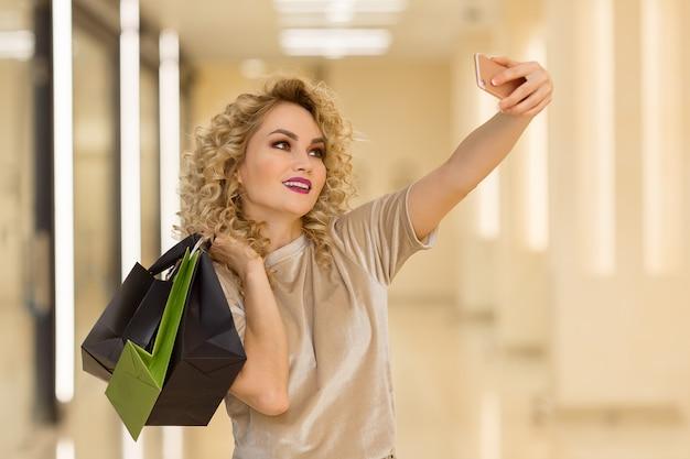 Feliz mujer bastante joven con bolsas de compras hace autorretrato de fotos en el teléfono inteligente