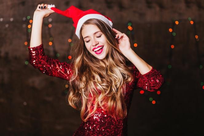 Feliz mujer blanca con pelo largo brillante posando con sombrero de santa claus