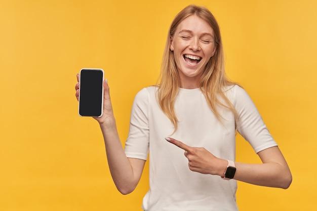 Feliz mujer bonita en camiseta blanca con pecas y reloj inteligente riendo y apuntando al teléfono móvil de pantalla en blanco en amarillo
