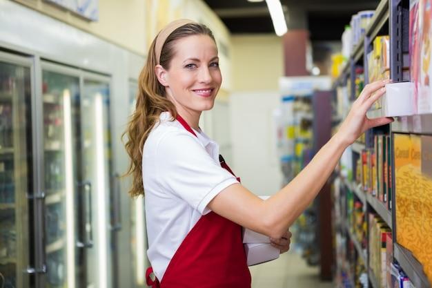 Feliz mujer bonita poner producto en el estante
