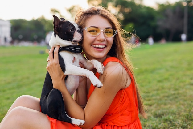 Feliz mujer bonita sentada sobre el césped en el parque de verano, sosteniendo el perro boston terrier, besos, vistiendo un vestido naranja, estilo moderno, jugando con mascotas