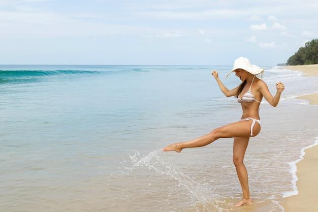 Feliz mujer está caminando en la costa del mar