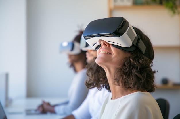 Feliz mujer caucásica en gafas de realidad virtual disfrutando de la experiencia