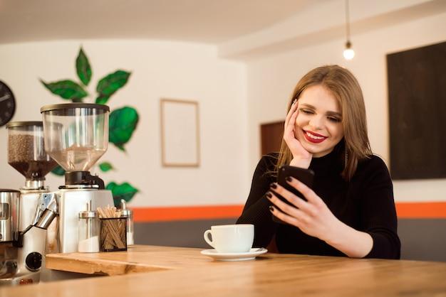 Feliz mujer caucásica mirando su foto en el teléfono celular mientras se relaja en la cafetería.
