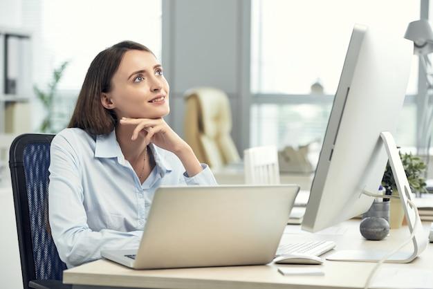Feliz mujer caucásica soñando en la oficina frente a la computadora portátil y pantalla grande