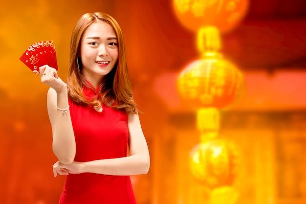 Feliz mujer china en cheongsam vestido y sobres rojos