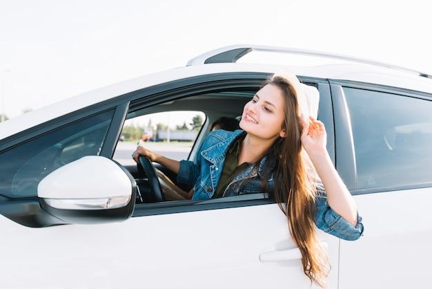 Feliz mujer colgando de la ventana del coche