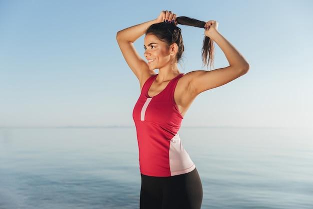 Feliz mujer deportiva preparándose para correr y corrige su cabello