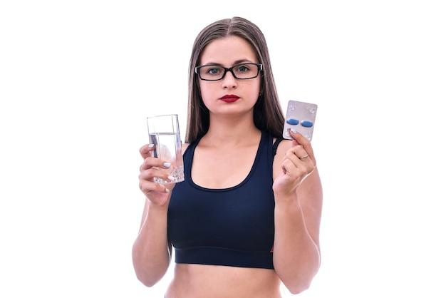 Feliz mujer deportiva sosteniendo ampollas con pastillas y vaso de agua