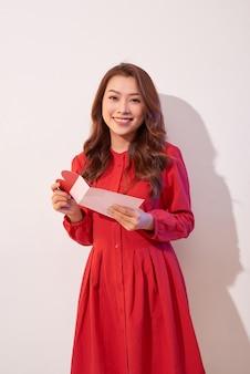 Feliz mujer disfrutando de la tarjeta de felicitación, leyendo con placer la carta de amor, celebrar el día de san valentín en casa