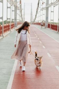 Feliz mujer elegante caminando con su corgi