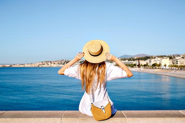 Feliz mujer elegante posando de nuevo, puso su mano en el aire y disfrutando de una vista increíble en francia